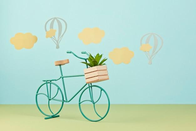 Manichino con nuvole di carta e palloncini volanti sopra lo sfondo blu pastello e bicicletta giocattolo