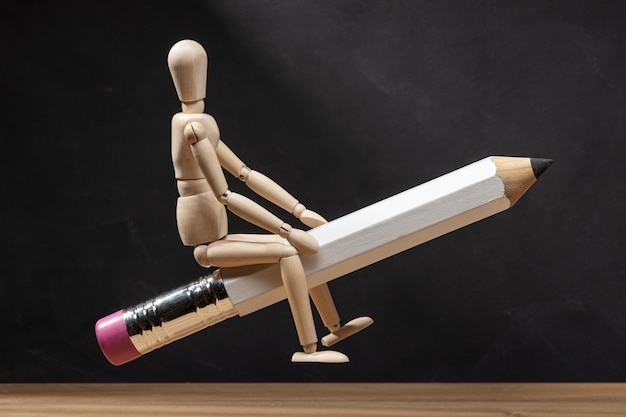 Manichino di legno in sella a una matita come un razzo. torna al concetto di scuola. copia spazio