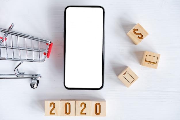 Manichino di smartphone, carrello, cubi con simboli
