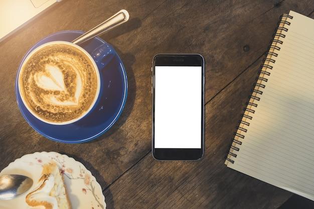 Manichino di smartphone con mobile schermo vuoto sulla scrivania in legno presso la caffetteria