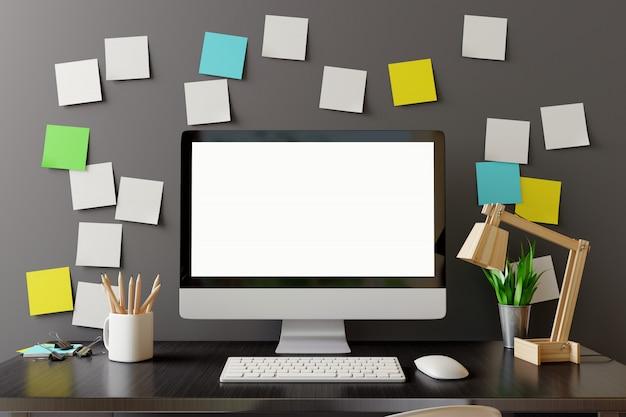 Manichino il computer dello spazio di lavoro con lo schermo in bianco sulla tavola nera.