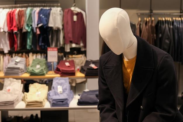 Manichino in autunno o cappotto invernale presso il negozio di abbigliamento maschile. tempo di stagione delle vendite e degli sconti.