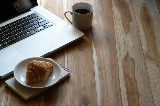 Manichino laptop, caffè e croissant sul tavolo da lavoro in legno.