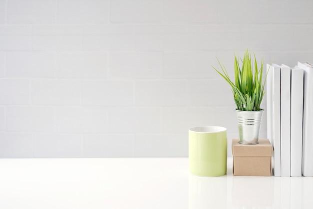 Manichino tazza verde, scatola di carta, pianta d'appartamento e libri sul tavolo bianco con muro di mattoni bianchi