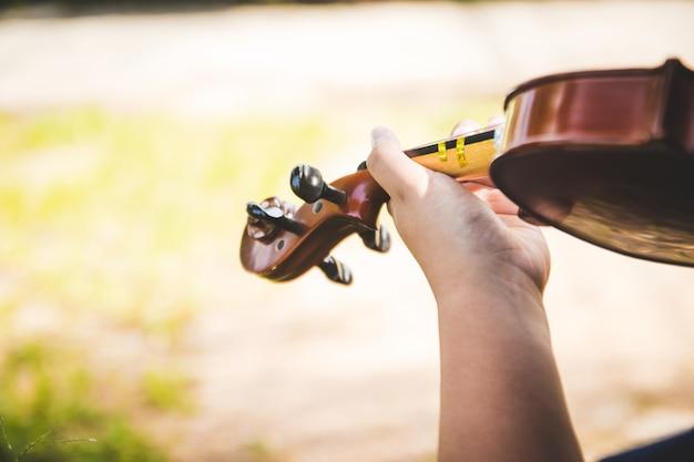 Manici del ragazzo del violino esercitati a giocare abilmente.