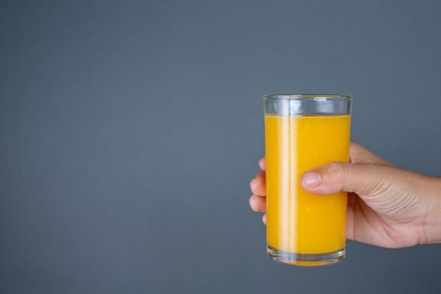 Manico in vetro con succo d'arancia.