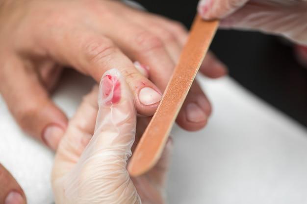 Manicure della ragazza che fa manicure per uomo nel salone di bellezza