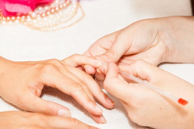 Manicure di unghie dalle mani di una donna prima di applicare lo smalto