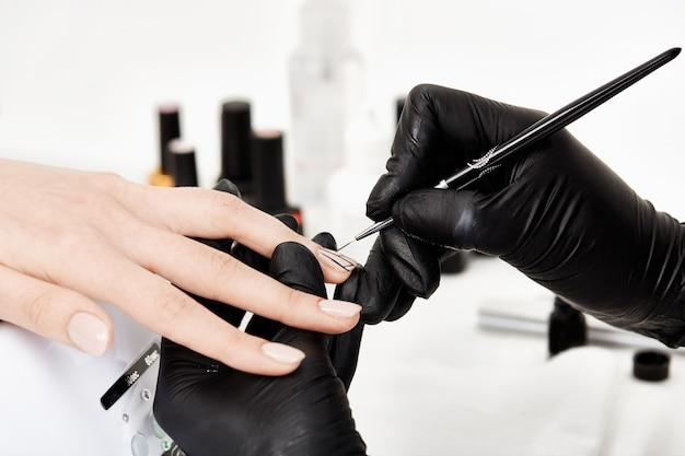 Manicure facendo nail art alla moda con pennello per manicure sottile.