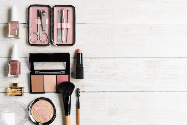 Manicure gli strumenti e gli strumenti in custodia rosa con smalto, cosmetici su fondo di legno bianco, vista dall'alto, copia spce, concetto di bellezza.