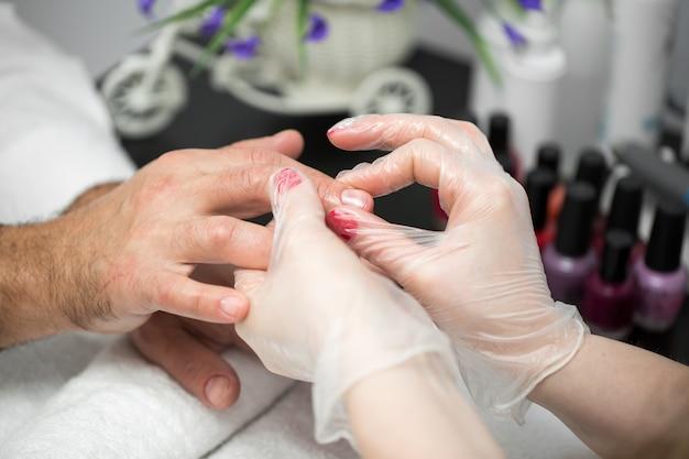 Manicure, mani spa olio per cuticole. il bello uomo passa il primo piano. unghie curate. mani di bellezza. trattamento di bellezza.