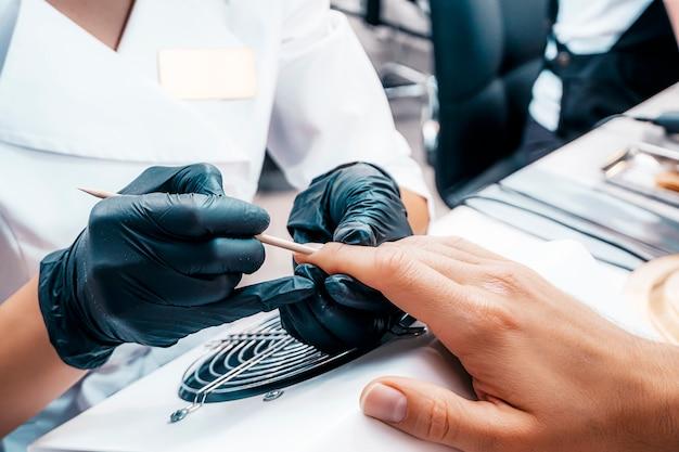Manicure manicure un uomo in un primo piano di studio di bellezza. primo piano ben curato delle mani del maschio.