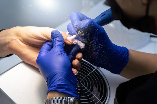 Manicure meccanica delle unghie sulle mani.