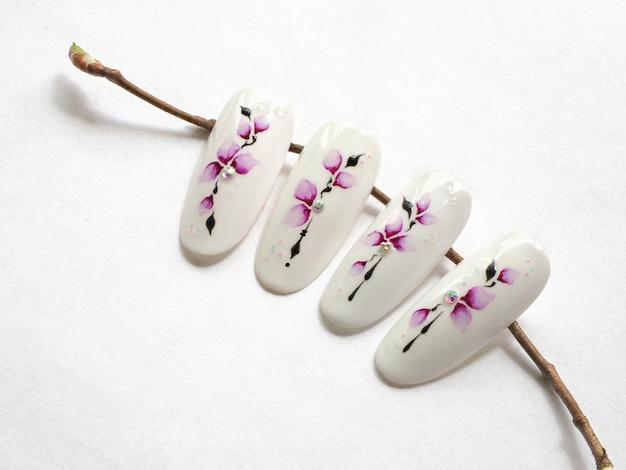 Manicure primaverile. suggerimenti con il disegno di fiori di primavera su un muro bianco