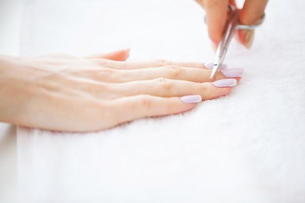 Manicure spa. donna in un salone per unghie che riceve una manicure da un'estetista
