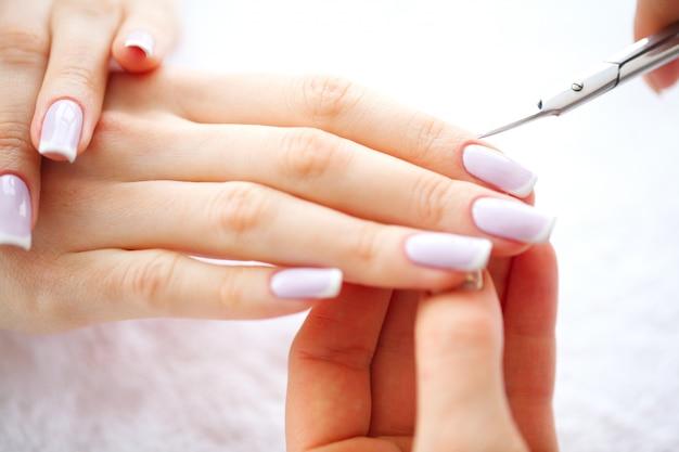 Manicure spa. manicure francese presso il salone spa. mani di donna in un salone per unghie che ricevono una procedura di manicure. procedura di manicure.