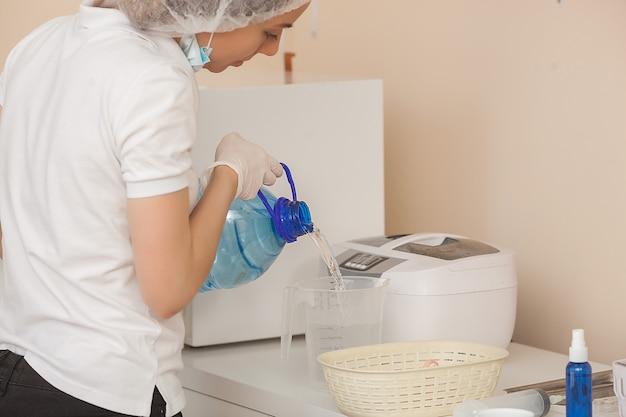 Manicure sterilizzare i suoi strumenti in autoclave o forno. padroneggia nel salone preparando i suoi strumenti per la disinfezione.