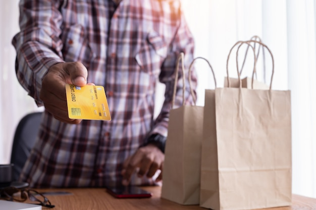 Manifestazione dell'uomo d'affari deridono il carrello di credito con il sacchetto della spesa.