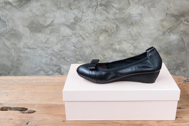 Manifestazione nera femminile delle scarpe sulla tavola di legno antica