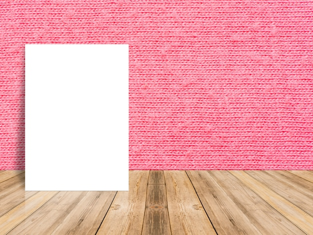 Manifesto bianco in bianco che si appoggia al tavolo in legno tropicale con parete di panno rosso.