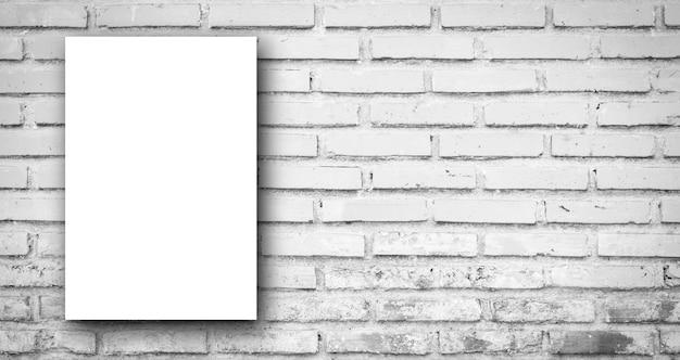 Manifesto bianco sul fondo panoramico della parete delle mattonelle del mattone di colore di tono grigio