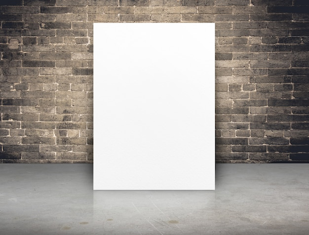 Manifesto in bianco del libro bianco al muro di mattoni del grunge e al pavimento di calcestruzzo