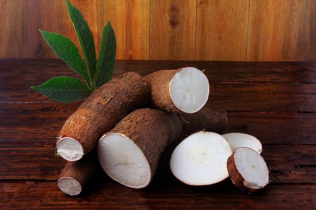 Manioca organica (mandioca, manioca, aipim, cucina brasiliana), sul tavolo di legno rustico