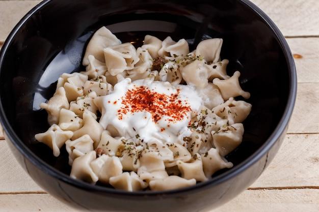 Manlama turco manti sul piatto con peperone, salsa di pomodori, yogurt e menta