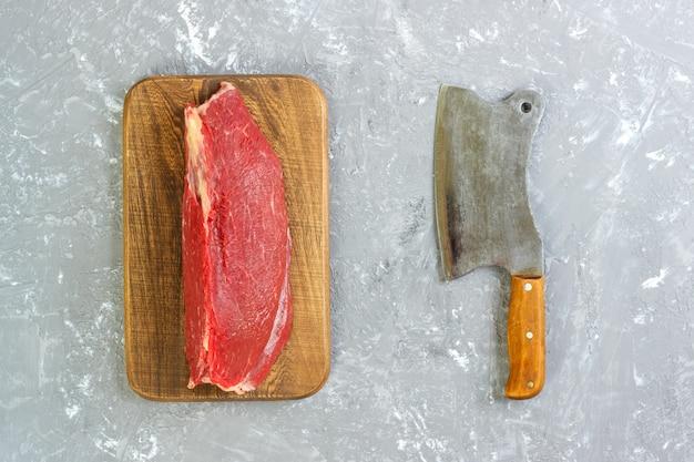 Mannaia d'annata e filetto di maiale crudo su calcestruzzo grigio