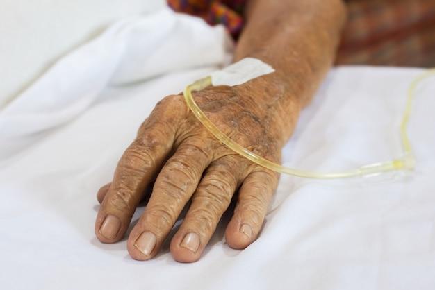 Mano anziani pazienti in ospedale con soluzione fisiologica per via endovenosa