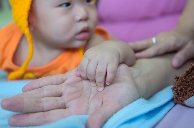 Mano asiatica del bambino sulla mano delle madri