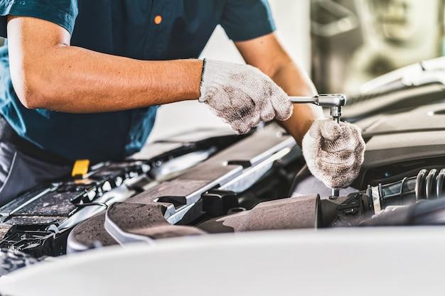 Mano asiatica del meccanico del primo piano che controlla e che ripara l'automobile nel centro di servizio di manutenzione