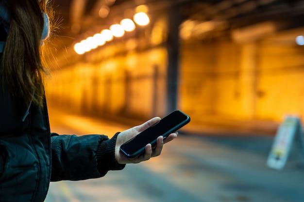 Mano asiatica del primo piano utilizzando il telefono cellulare intelligente nel terminal sunway con scarsa luminosità, tecnologia e business, comunicazione e messaggio, trasporto pendolari di trasporto ferroviario