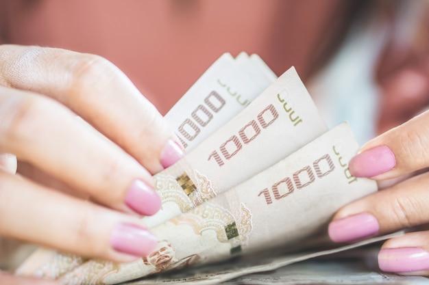 Mano asiatica della donna che conta valuta di carta di baht tailandese dei soldi
