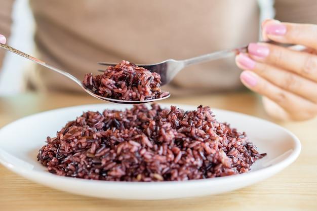 Mano asiatica della donna che mangia la bacca sana del riso