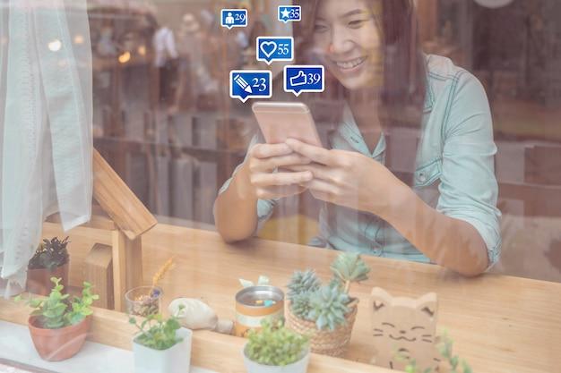 Mano asiatica della donna di affari facendo uso del telefono cellulare astuto per i media sociali del netwrok con il numero di simili