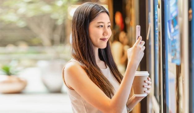 Mano asiatica della giovane donna facendo uso del telefono cellulare astuto che esplora la macchina dei biglietti di film