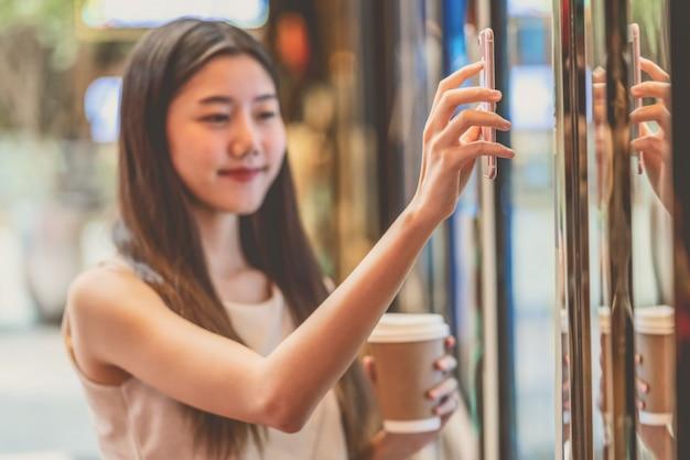 Mano asiatica della giovane donna facendo uso del telefono cellulare che esplora la macchina dei biglietti di film