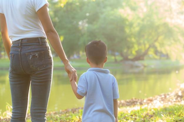 Mano asiatica della tenuta della madre o del genitore e del figlio con amore insieme