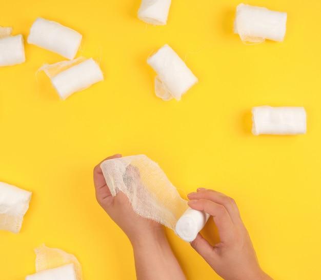 Mano avvolta con una benda di garza bianca su giallo