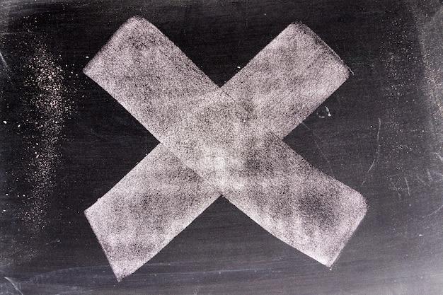 Mano bianca del chak di colore che assorbe l'incrocio o forma di x sul fondo della lavagna