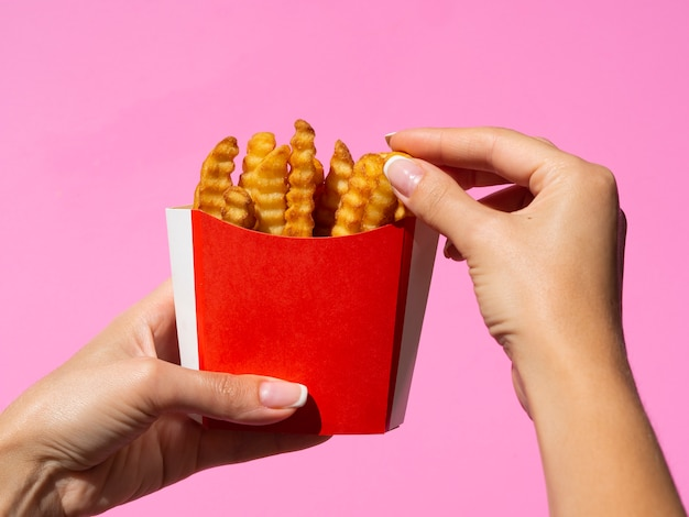 Mano che afferra le patate fritte con fondo rosa