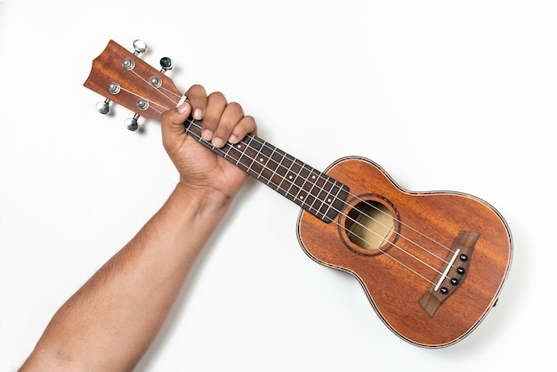 Mano che afferra un ukulele di legno