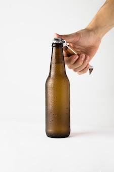 Mano che apre la bottiglia di birra