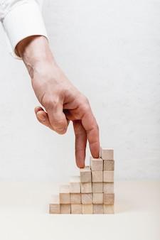 Mano che fa un passo sul concetto di legno dei cubi
