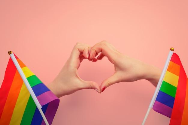Mano che fa un segno del cuore con bandiera arcobaleno di orgoglio gay lgbt