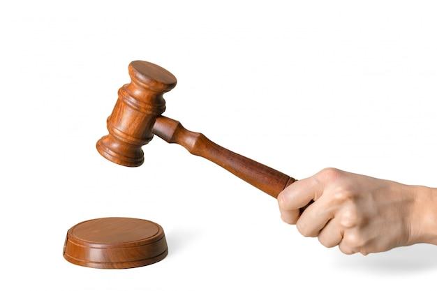 Mano che giudica il martelletto di legno di legge isolato