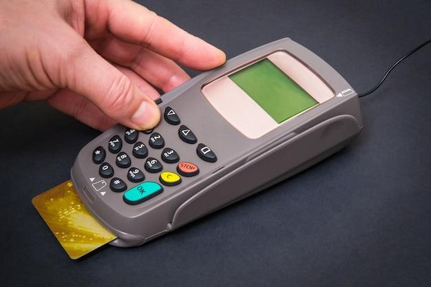 Mano che immette il codice pin al terminale di denaro prima del pagamento
