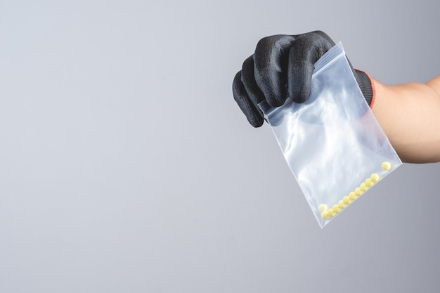 Mano che indossa un guanto scuro che tiene droghe illegali in un sacchetto di plastica con cerniera come trafficante di contrabbandieri