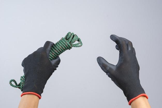 Mano che indossa un guanto scuro e tiene in mano un cavo verde per paracadute di corda di nylon